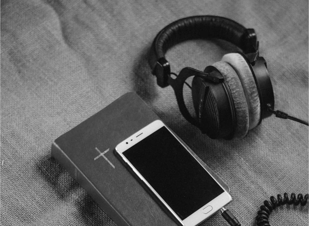 Bible, Phone and Headphones listening to podcast